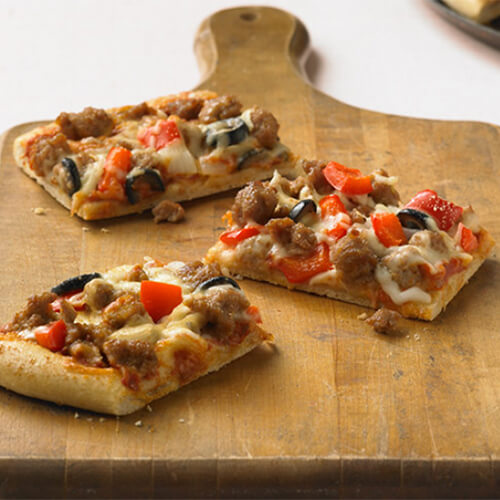 3 squares of Sicilian pizza topped with turkey, red bell pepper and olives on a wooden pizza board, with a pink background.