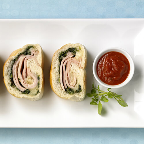 3 Strombolis baked into a flaky crust filled with spinach and provolone with a side of marinara to dip, on a white platter in a blue tablecloth.