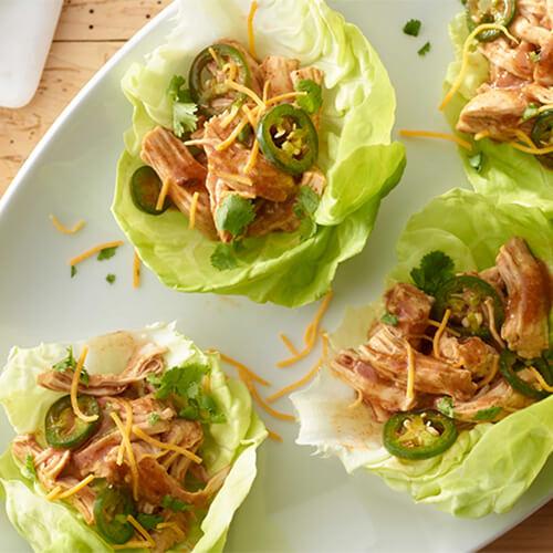 Four lettuce wrapped turkey enchiladas, topped with jalapeno.