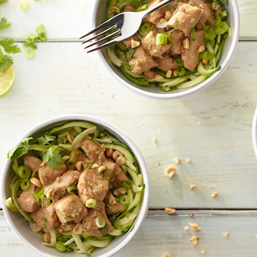 Two white bowls of Thai peanut turkey and zucchini noodles on a white wooden background.