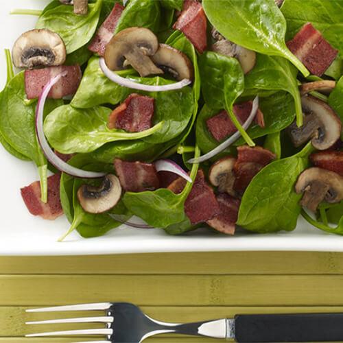 Spinach, JENNIE-O® Turkey Bacon salad on a white plate.