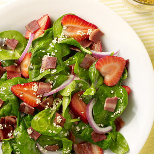 A fruity, filling, salad filled with Fresh strawberries, turkey bacon, and baby spinach, served with a vinaigrette, in a white plate on a yellow lined tablecloth.