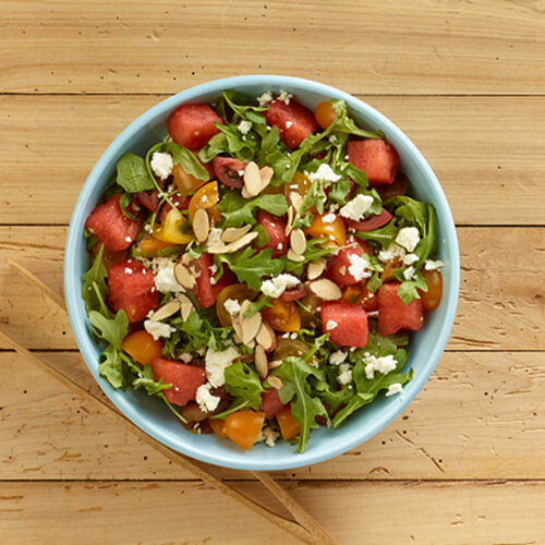 Watermelon, arugula, and tomatoes, garnished with almonds and feta, served in a blue bowl atop a wooden table.