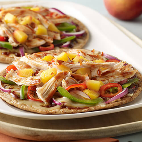 2 sweet flatbread pizzas, topped with barbecue sauce, peppers, and shredded turkey, displayed on a white tray.