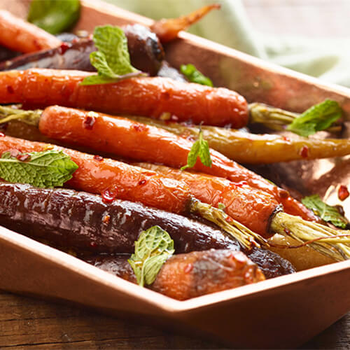 Sweet honey chili glazed carrots garnished with mint on a white tray.