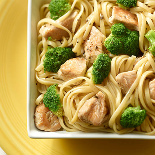 Lean turkey breast tenderloins, broccoli florets, and creamy sauce, served in a bed of linguine pasta, in a white bowl on a yellow tray.