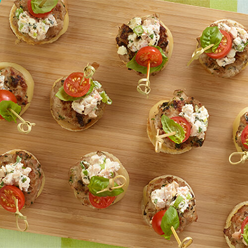 Tasty turkey sliders topped with savory turkey cream cheese and crumbled feta served on a wooden board, atop a colorful tablecloth.