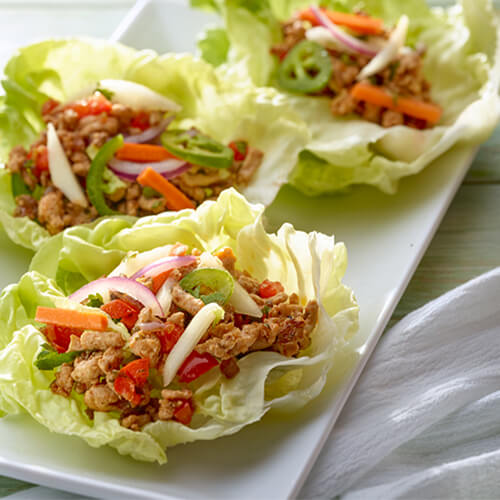 Turkey with lettuce wraps on a white plate.
