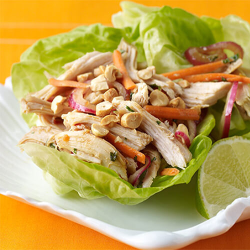 A flavorful lettuce wrap filled with turkey, peanuts, and vegetables, served with a lime wedge, on a white plate.
