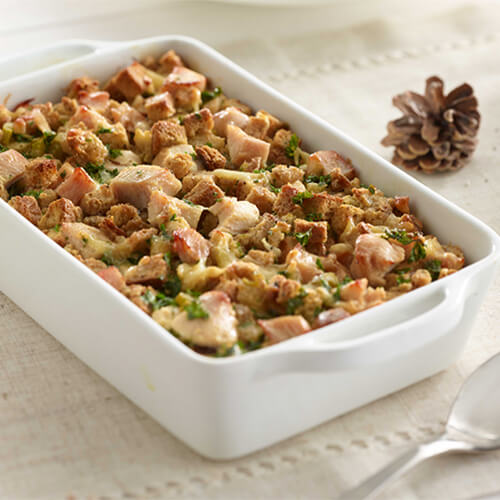 Thanksgiving breakfast egg strata casserole in a white baking dish next to a pinecone.