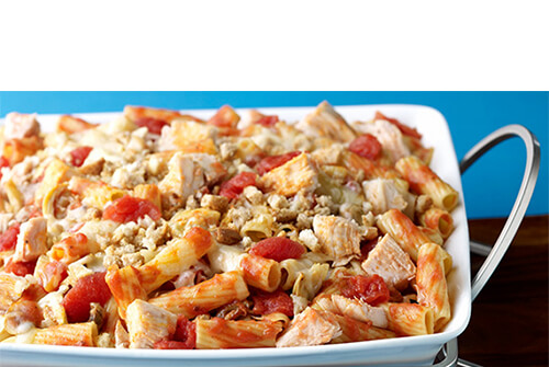 A pasta bake chock full of veggies made with Cheddar, mozzarella and parmesan baked with rigatoni and lean turkey. on a white casserole tray.