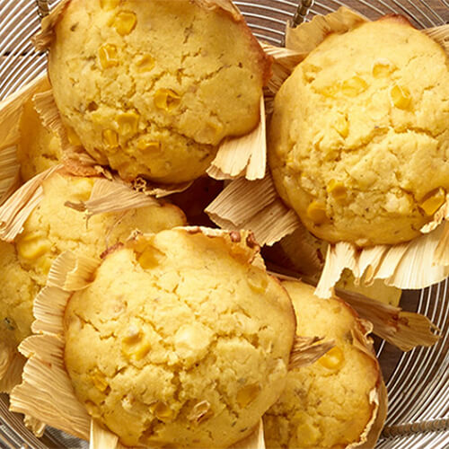 Cornmeal muffins featuring fresh whole kernel corn, cooked in cornhusks, served in a wired bowl atop a wooden table.