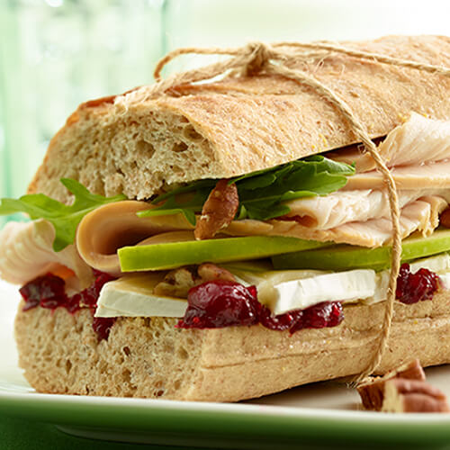 A sandwich filled with fresh arugula, thinly-sliced green apples, crunchy pecans, lean turkey breast, Brie cheese and swimming in a savory cranberry chutney, served on a white plate.