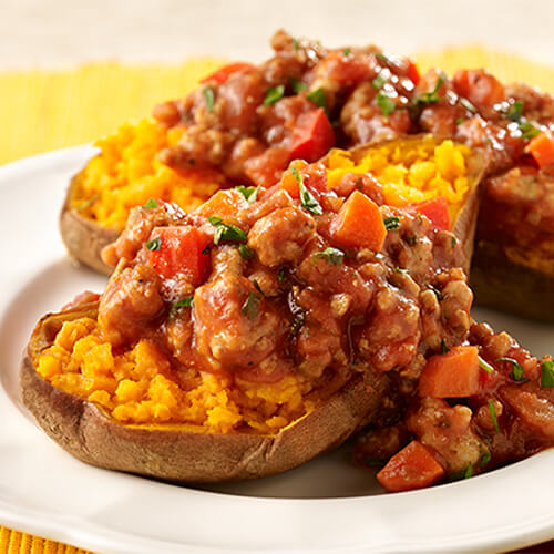 Sweet potatoes filled with turkey, tomato sauce, and more sloppy joe fixins, served on a white plate.