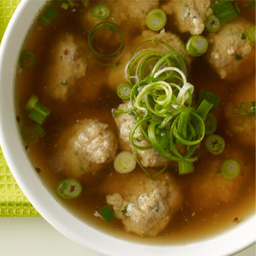 A savory soup with ground turkey, shrimp, cilantro and garlic dumplings simmered in a flavorful hoisin and lemongrass broth, served with a side of chopped green onions, on a white bowl, on a green cloth.