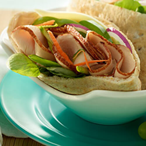 Pita pockets loaded with fresh spinach, zucchini, carrots, green pepper and lean turkey breast filled with chipotle mayo and served on a blue bowl, with a side of grapes.