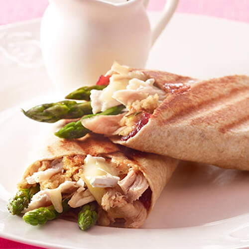An amazing omelet filled with melted brie, Cajun-style lean turkey breast and fresh asparagus encased in eggs, served in a pan on a white cloth and table.