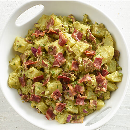 A hearty potato salad made with turkey bacon, guacamole, and jalpaneo served in a white bowl atop a wooden table.