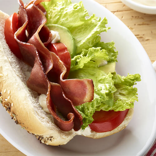 Turkey bacon, lettuce, and tomato on a bun on a white plate.