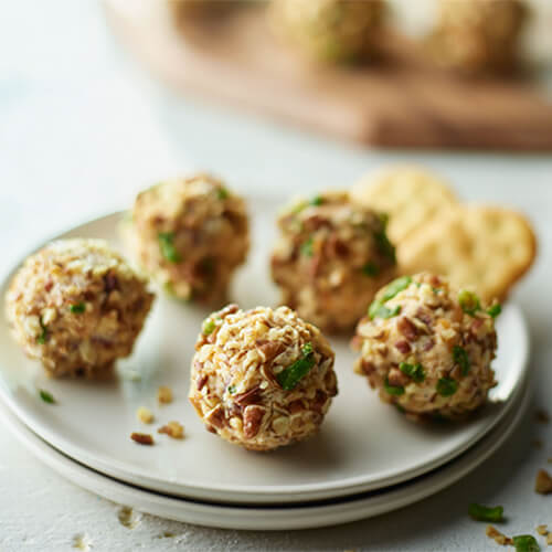 Turkey bacon cheese balls on a grey plate sitting on a white wood table.