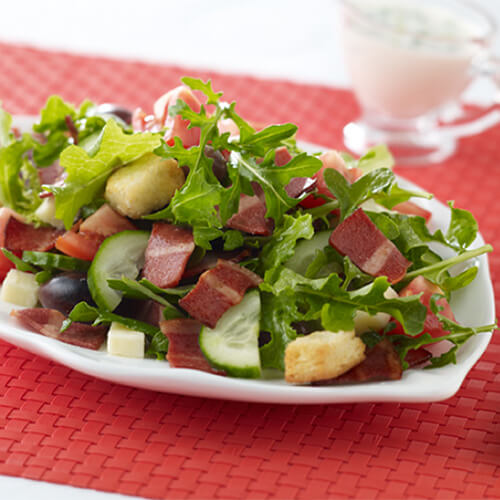 A bunch of leafy greens with JENNIE-O® Turkey Bacon and tomatoes.