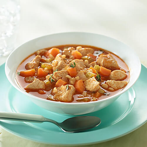 Lean turkey and barley soup filled with carrots, celery and fresh thyme, served on a white bowl with bread and a blue plate.