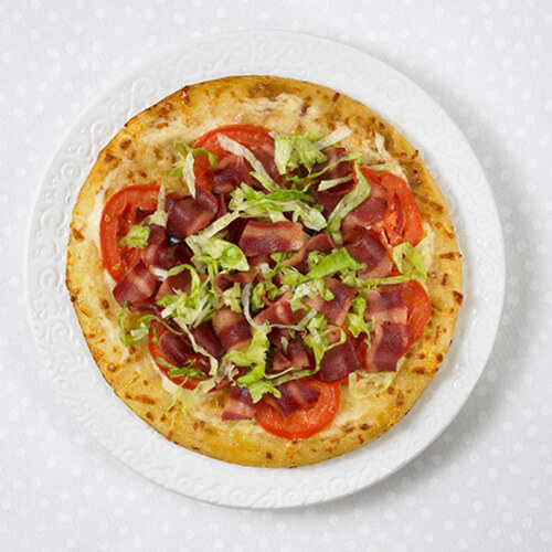 Homemade pizza topped with tomatoes, lettuce, and JENNIE-O® Turkey Bacon on a white plate.