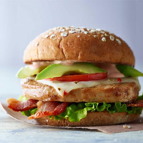 Turkey burger club on a marble slab with a grey background.