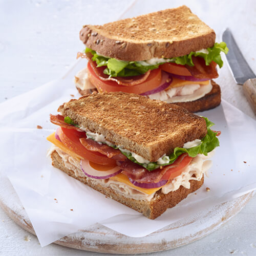 A crispy sandwich with turkey breast, crispy turkey bacon, vegetables and a dash of horseradish mayo.