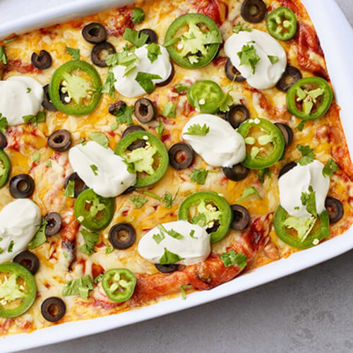 Turkey enchilada lasagna with jalapeno dolloped with sour cream in a white baking dish.