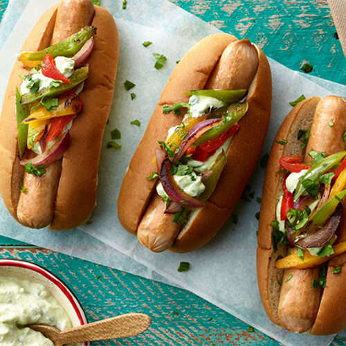 Three fajita turkey dogs topped with bell peppers and onions on a white background.