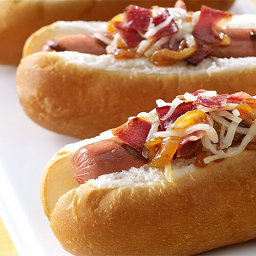 Juicy turkey franks topped with barbecue sauce, cheese, caramelized onions, and bacon, served on a white tray.