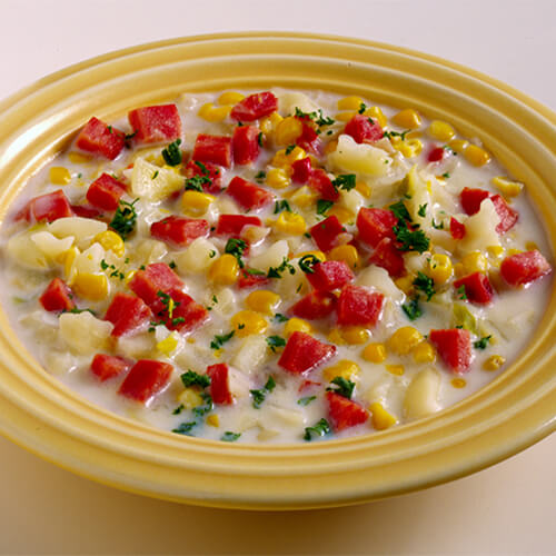 A rich, creamy chowder made with corn, bell peppers, potatoes, and turkey ham, in a yellow bowl, garnished with parsley.