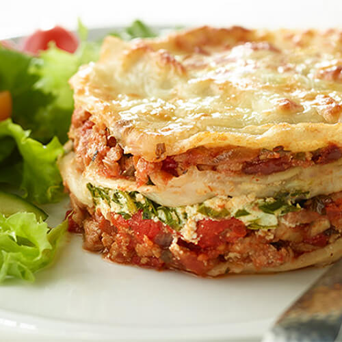 A cupcake-sized lasagna filled with ground turkey, cheese, tomato sauce, and vegetables, served on a white plate with a side of salad.