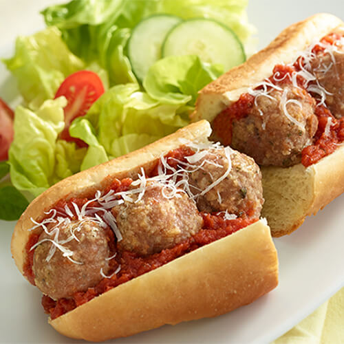 A hearty amount of turkey meatballs, parmesan cheese, and swimming with pasta sauce, served on a submarine roll on a white plate, garnished with a salad.