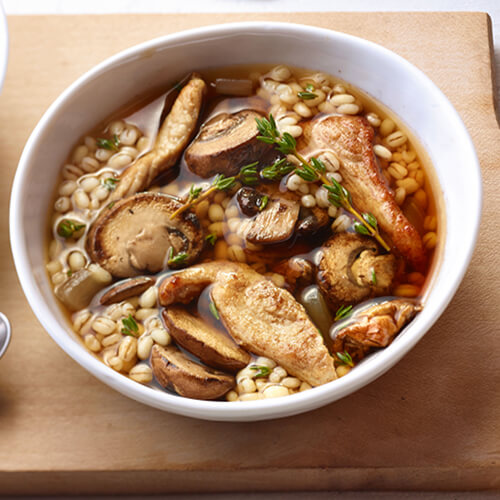 Turkey breast, mushrooms, and barley soup in a white bowl on a wooden background.