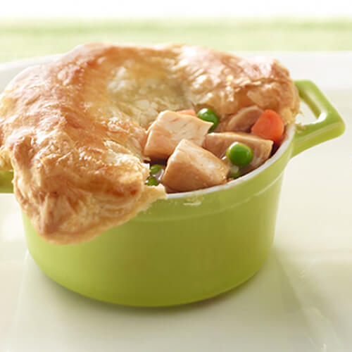 A flaky puff pastry baked with turkey breast, peas, carrots and gravy, served in green miniature bowls on a white platter.