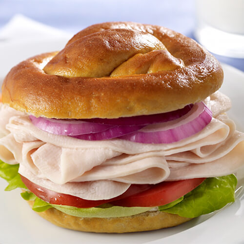 A hearty pretzel roll filled with lettuce, tomato, onion and turkey, served with mustard on a white plate with a side of carrots.