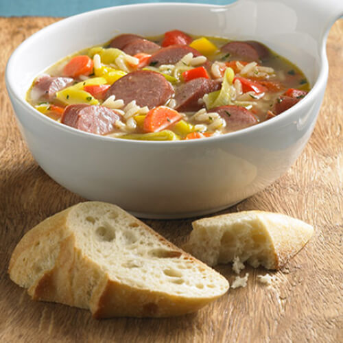 JENNIE-O® Turkey Sausage bowl with rice and vegetables next to a hunk of bread.
