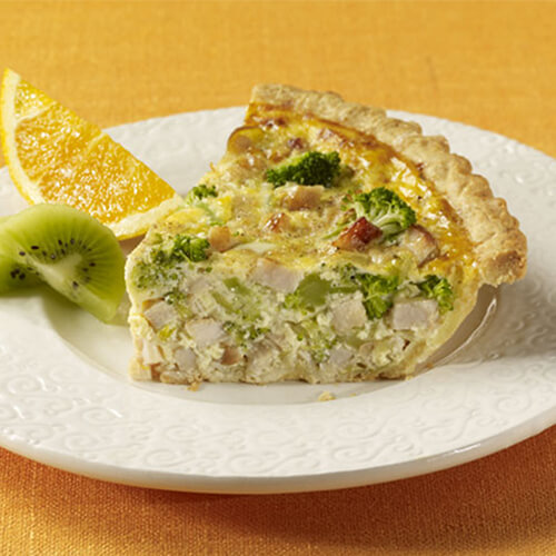 A hearty slice of quiche filled with turkey, leek, and spinach with a side of kiwi slices and a lemon wedge, in a white plate with a yellow background.