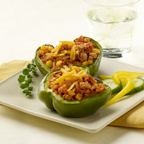 Colorful bell peppers filled with rice, corn, ground turkey, and topped with melted Cheddar, served with cucumbers and lemon on a white tray on a white table, served with a glass of water.