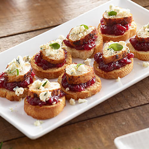 Turkey tenderloin crostini sprinkled with cheese arranged on a white plate.