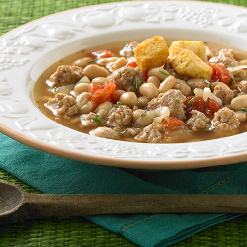 White bowl of JENNIE-O® Turkey with tuscan beans and tomatoes on a green napkin.