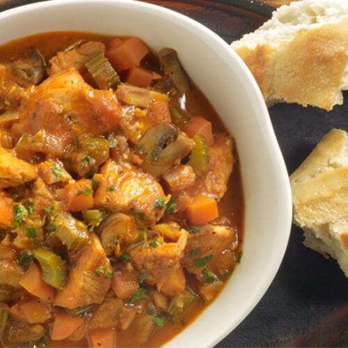 A savory soup, packed to the brim with veggies and turkey in a white bowl, served with torn bread on a wooden plate.