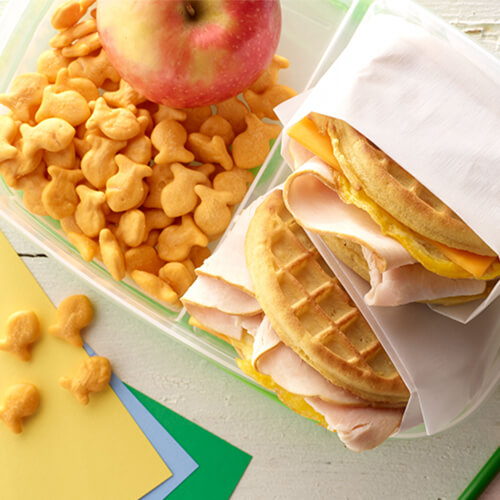 Turkey waffle sandwiches with golden fish crackers and an apple on a white plate.