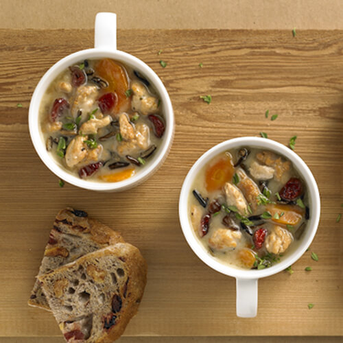Two mugs filled with turkey, wild rice, and vegetables and Herb-Ox chicken bouillons with a side of slices of olive bread on a wooden platter with a yellow napkin on a tan background.