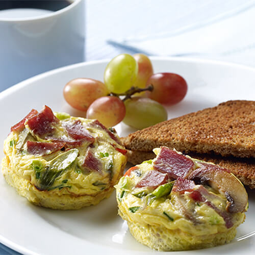 2 hearty frittatas chock full of vegetables, turkey bacon, and Swiss cheese, served on a white plate with a side of toast and grapes.