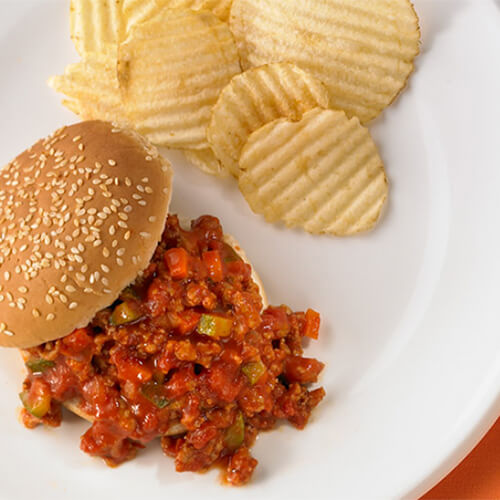 Turkey-based sloppy joes packed with vegetables such as zucchini, tomatoes, and carrots on a sesame seed bun, with a side of crinkle-cut potato chips served on a white plate, on a orange tablecloth.