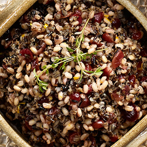 Wild rice and barley paired with cranberries and orange zest, served in a painted bowl atop a wired tablecloth.