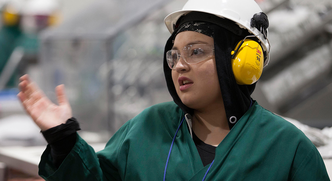 A JENNIE-O® factory worker in full protective gear going about her work day.